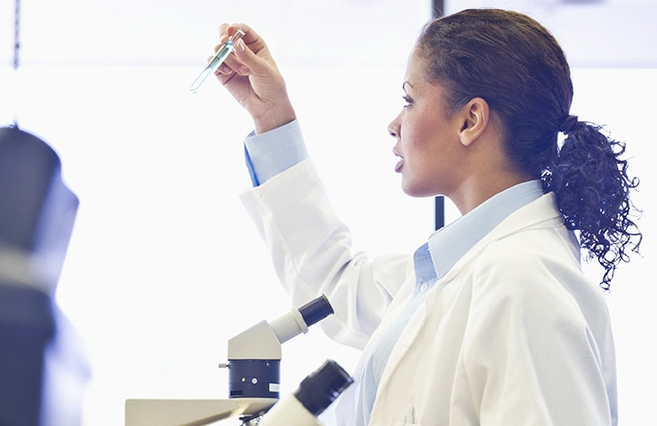 A optometrist in a lab coat inspecting a test tube