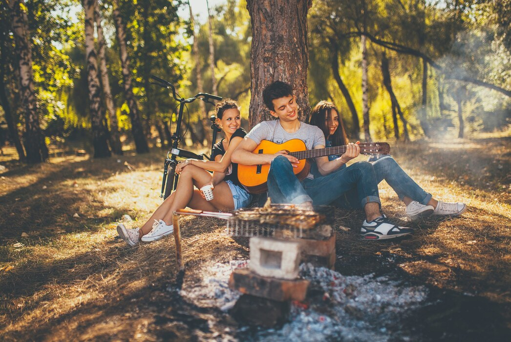 A young man sitting under the tree with two girls, playing a guitar