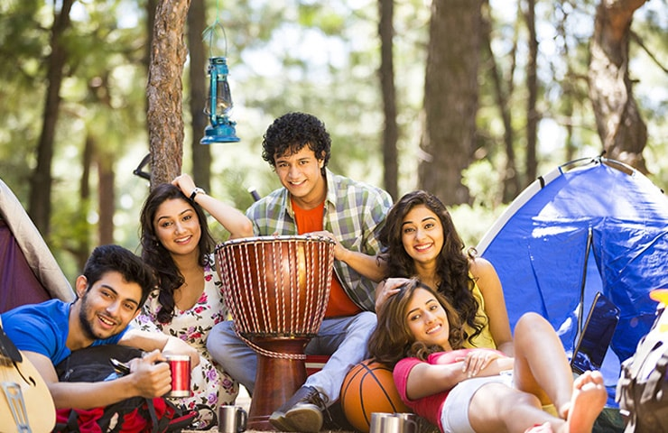 A group of friends sitting in the woods with a big drum in the centre