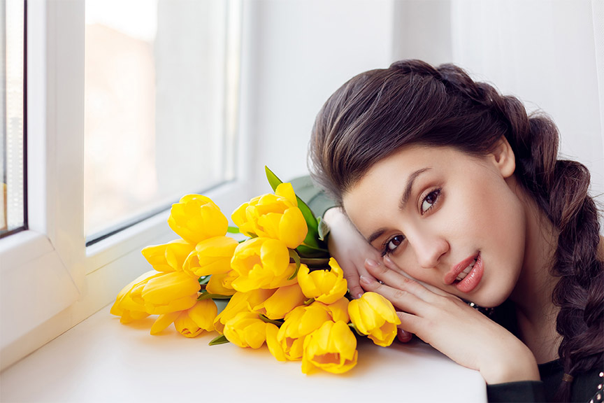 A woman resting her head on yellow flowers, looking at the camera