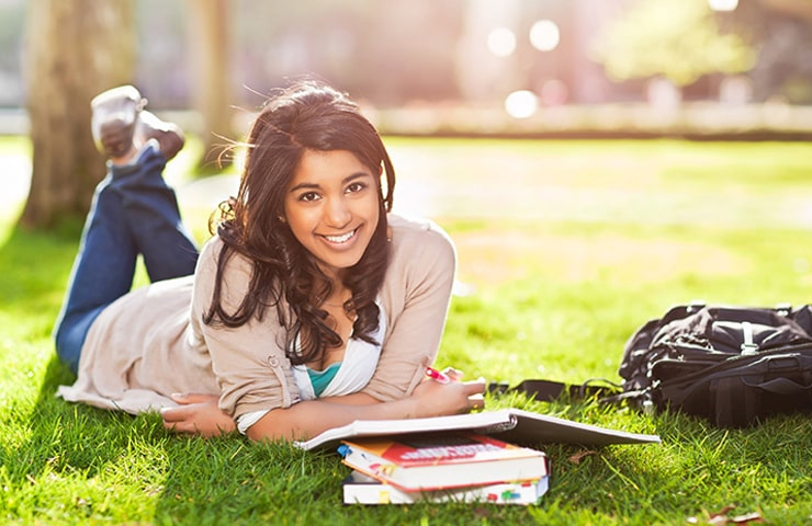 A girl lying on the grass with her books, smiling at the camera